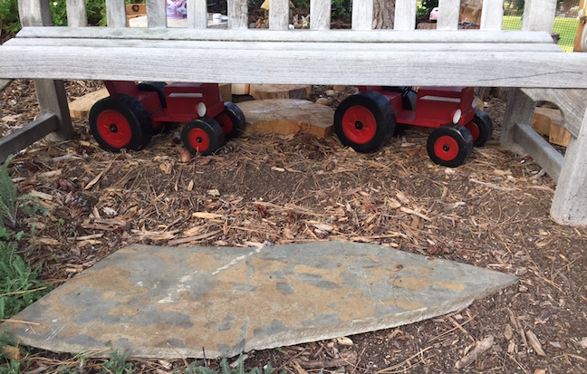 Toy tractors hide under one of garden's benches