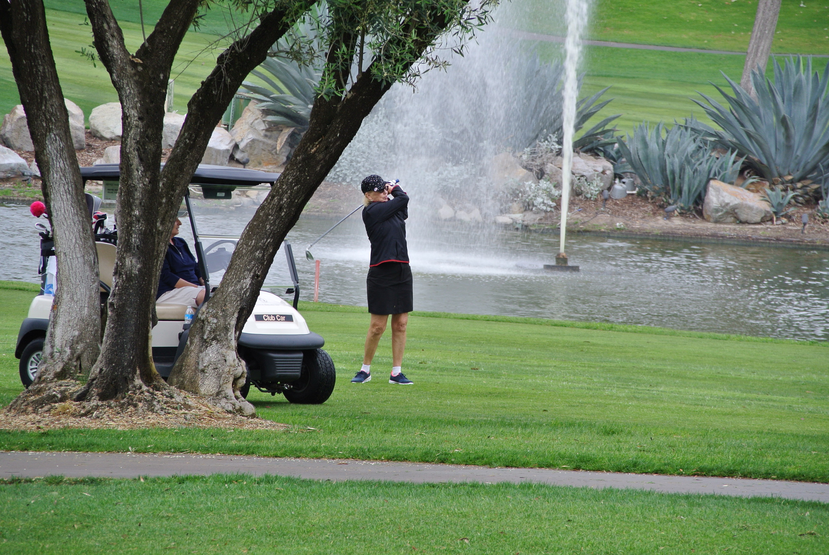 Player completes her approach shot on No. 18, with water spout in background